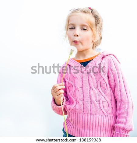 6-year-old beautiful girl blowing dandelion - stock photo