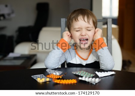 4 year old boy crying before swallowing medication at home - stock photo