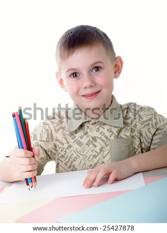 6 year old boy draws pencils sitting for a table