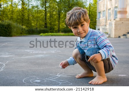 4 year old boy draws with chalk on asphalt