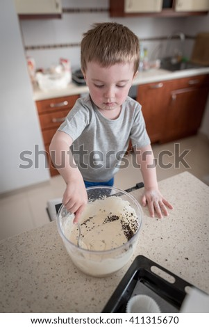 2 year old boy having fun preparing dough for muffins with chocolate chips in kitchen at home - stock photo