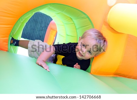 2 year old boy jumping onto an inflatable bouncy castle - stock photo