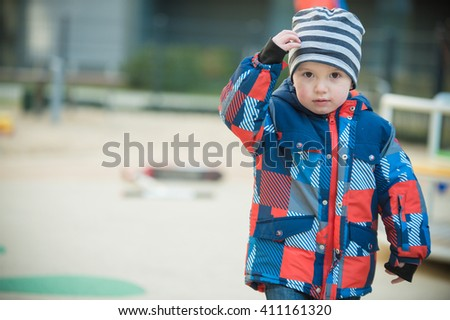 2 year old boy looking at camera on playground - stock photo