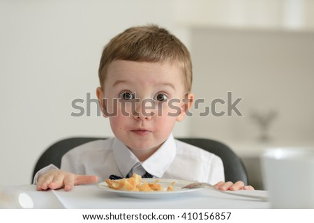 2 year old boy looking at camera with dessert cake on plate in front of him during family meeting.