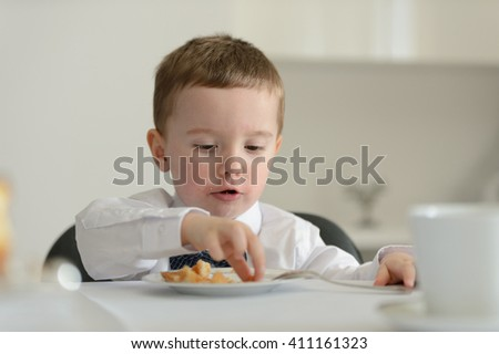 2 year old boy looking at camera with dessert cake on plate in front of him during family meeting