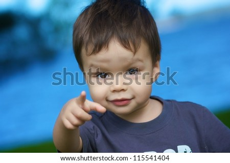 1 year old boy looks and points directly at the camera with blue water and green grass in background - stock photo