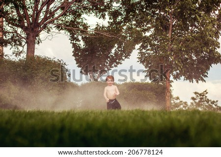3 year old boy playing in the sprinklers on a hot day -- image taken outdoors in Reno, Nevada, USA