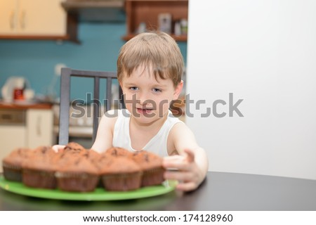 4 year old boy reaching for a chocolate cake at home - stock photo