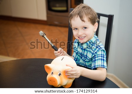 4 year old boy wants to break the piggy bank with a hammer - stock photo