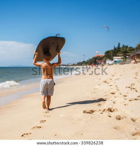 4 year old boy with a surfboard - stock photo