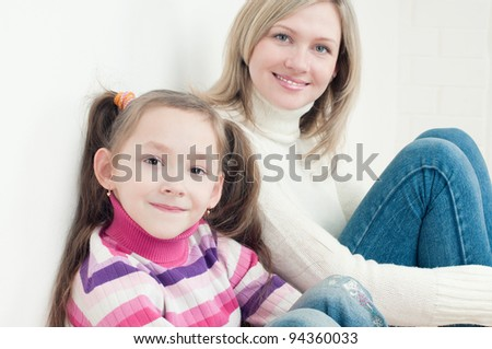 7-year old caucasian girl and her mother smiling and looking at camera