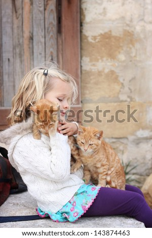 6 year old child holding two ginger cats