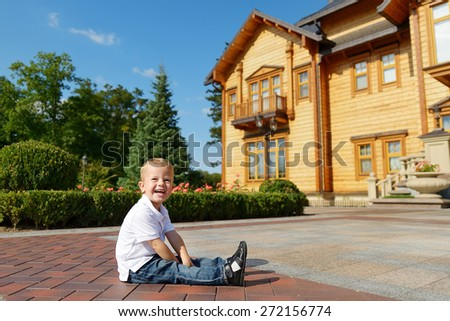 2 year old child in a city park on a background of elegant wooden house, in blue jeans and a white t-shirt. Blond boy with blue eyes. Cheerful child in the summer park. Laughing baby in nature. - stock photo
