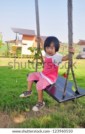 2 year old child playing swing in the green mountain