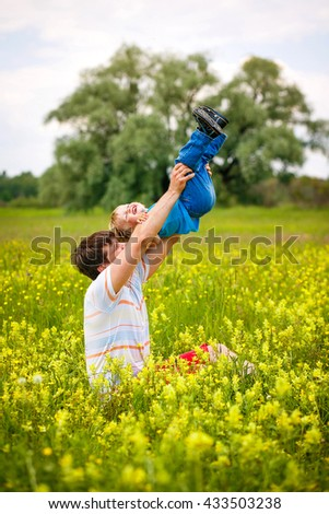 2-3-year-old cute boy having fun with his father on the field with yellow flowers. - stock photo