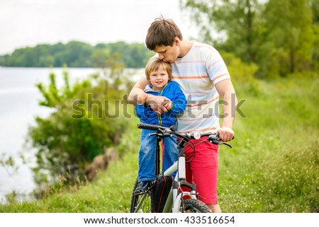 2-3-year-old cute boy with his father are on the river side with bicycle. - stock photo