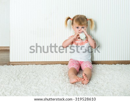 2-year-old girl  drink the milk on the floor in her home - stock photo