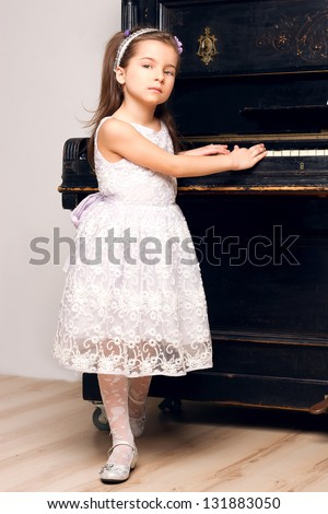 5 year old girl in a black dress stands near the piano - stock photo