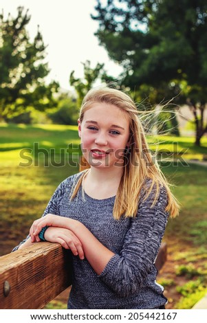 11 year old girl standing by a fence while at the park with her family -- image taken outdoors at San Rafael Park in Reno, Nevada, USA