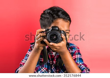 10 year old indian boy holding digital camera or DSLR camera, posing like a professional photographer, young photographer, kid photographer, child photographer, portrait, closeup, red background - stock photo