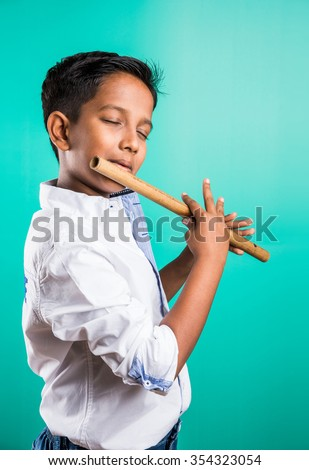 10 year old indian boy playing flute, indian boy and music, indian boy learning music, indian boy with musical instrument, brown indian boy - stock photo