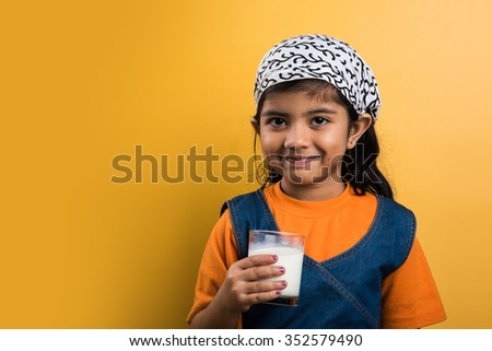 4 year old indian girl with a glass full of  plain white milk, indian girl and plain milk, indian girl drinking milk, asian girl and milk glass, portrait, brown skin, indian baby girl - stock photo