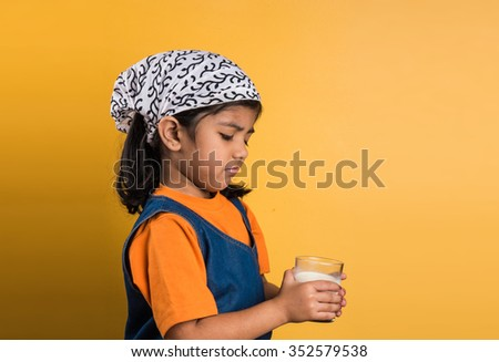 4 year old indian girl with a glass full of  plain white milk, indian girl and plain milk, indian girl drinking milk, asian girl and milk glass, portrait, brown skin, indian baby girl, tantrums - stock photo