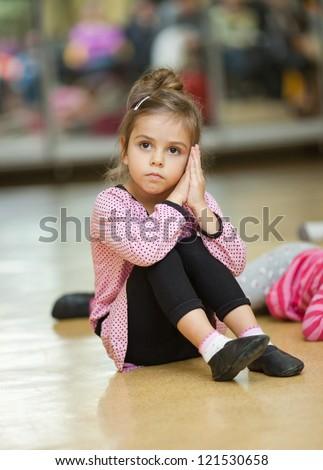 5 year old little girl doing dance exercises on the floor - stock photo
