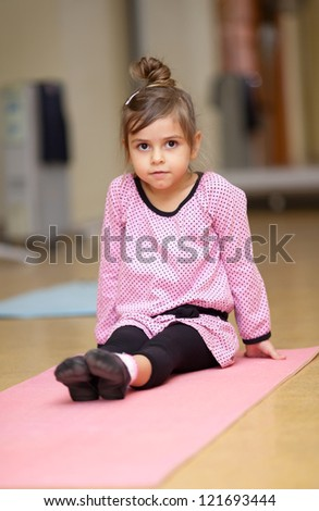 5 year old little girl doing sports exercises on the mat - stock photo
