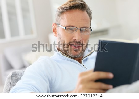 40-year-old man relaxing in sofa reading book - stock photo