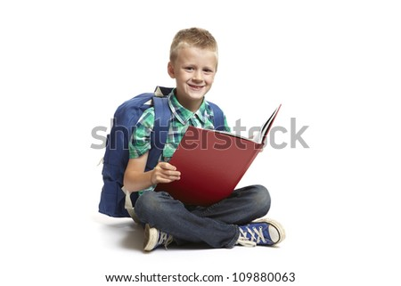 8 year old school boy with backpack sitting reading a red book on white background