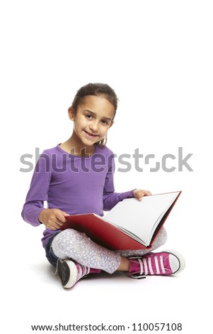 8 year old school girl sitting reading book smiling on white background - stock photo