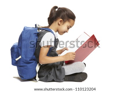 8 year old school girl sitting reading book with backpack smiling on white background - stock photo