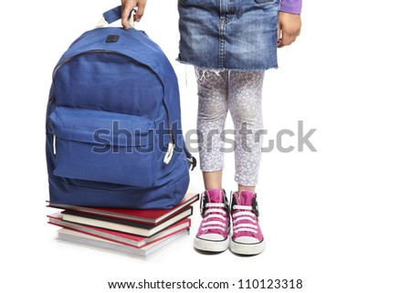 8 year old school girl with books and backpack on white background - stock photo