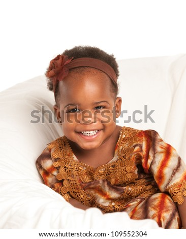 3 year old Smiling  African American girl in Colorful Costume sit on bed - stock photo