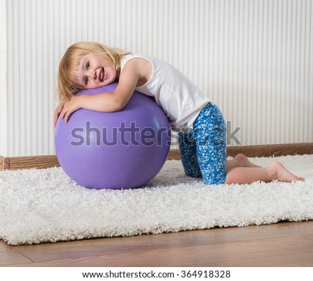 3-year-old  smiling girl with african braids on the ball for fittnesa at home - stock photo