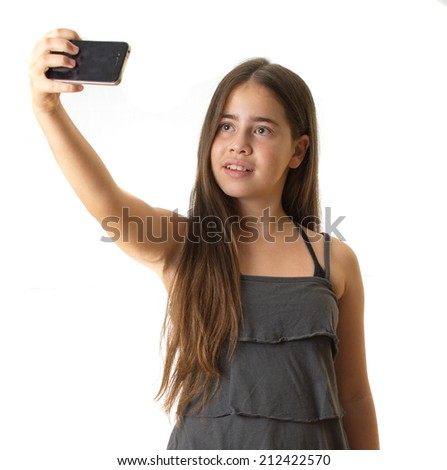 12 year old teenage girl taking a selfie - self portrait with her smartphone - isolated on white - stock photo