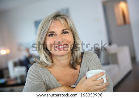 50-year-old woman at home drinking tea - stock photo