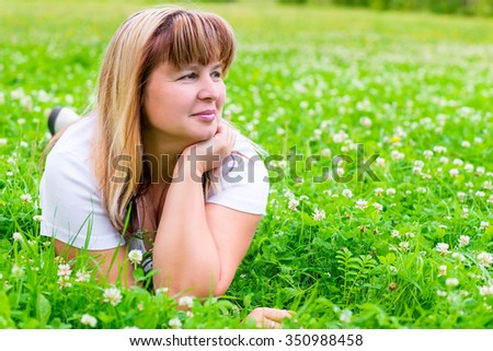 50-year-old woman on a green meadow looking to the side - stock photo
