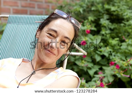 40 year old woman resting in the garden - stock photo