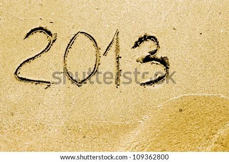 2013 year on the sand beach near the ocean - stock photo