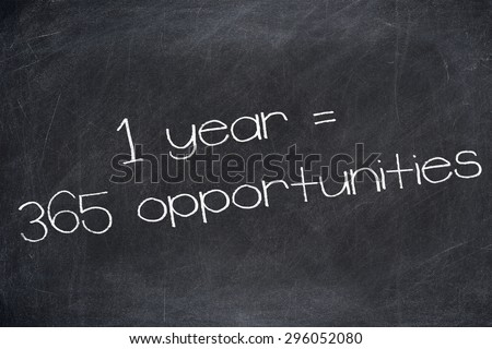 1 YEAR = 365 OPPORTUNITIES motivational quote written on blackboard. - stock photo