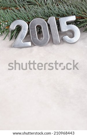 2015 year silver figures on a spruce branch