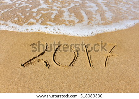 2017 year written on sandy beach sea