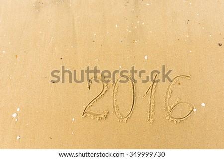 2016 Year written on the beach. sand background - stock photo