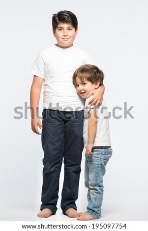 4 years and 9 years kids, brothers posing in standing position and hugging each other - stock photo