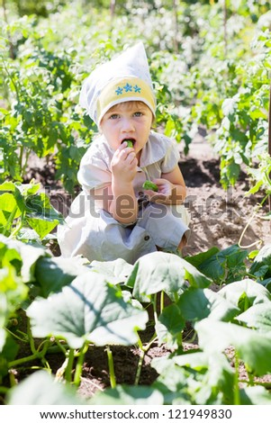 2 years baby girl eats cucumbers at plant - stock photo