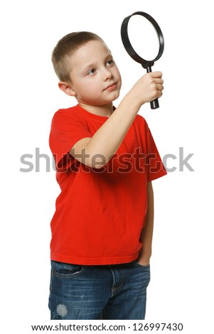 6 years boy looking through the magnifying glass over white background - stock photo
