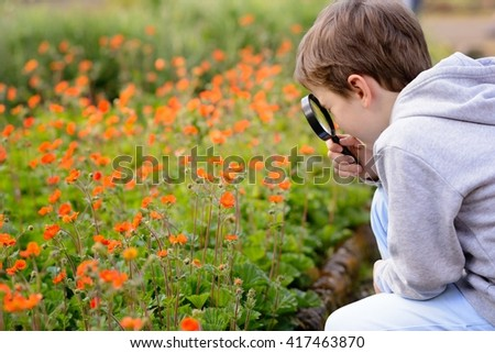 7 years boy looks at the colorful flowers in the park through a magnifying glass - stock photo