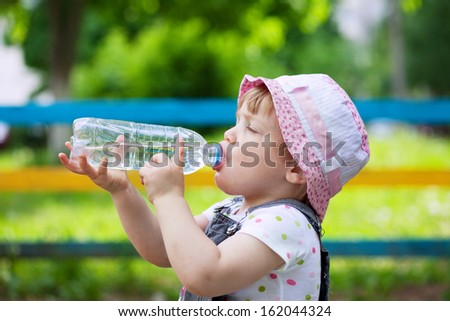 2 years child drinks from plastic bottle in park - stock photo